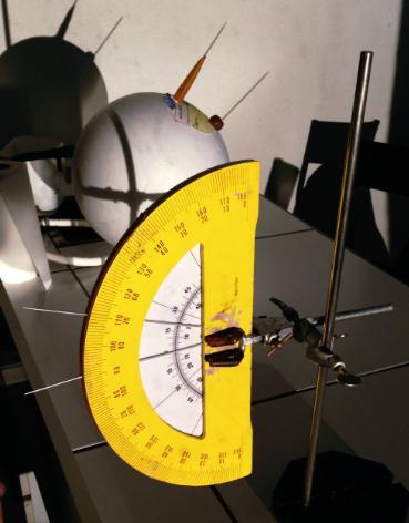 Un rapporteur représente la Terre en coupe, et deux baguettes sont placées dans le plan vertical